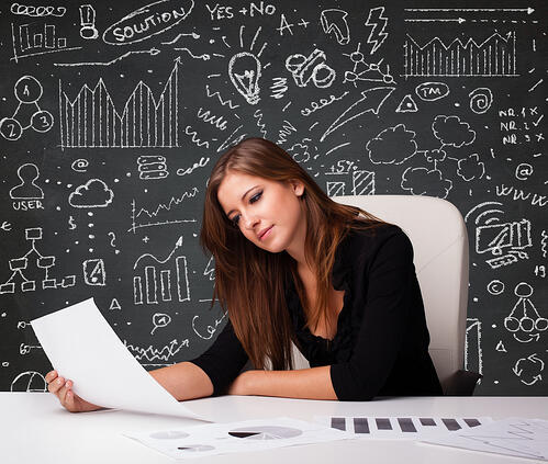 Pretty young businesswoman sitting at desk with business scheme and icons